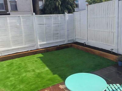 new flowerbeds, astro turf, painted fence