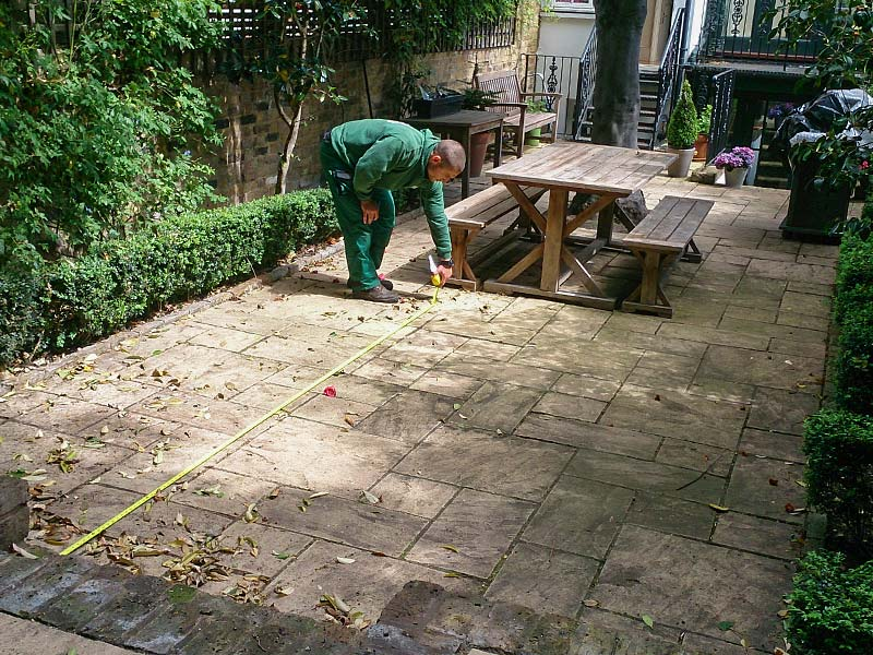 gardener inspecting a patio nw6