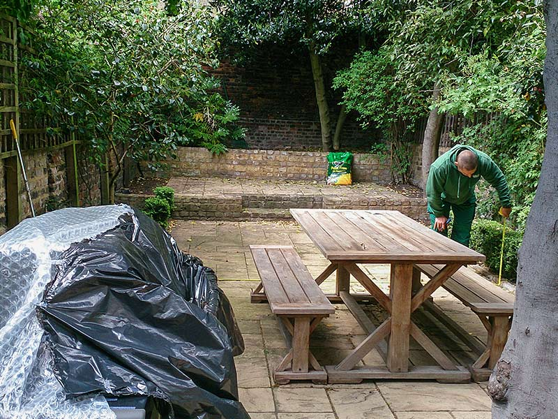 patio area being measured by a gardener