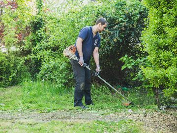 gardener cutting grass in West Norwood