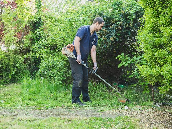 gardener cutting grass in West Norwood